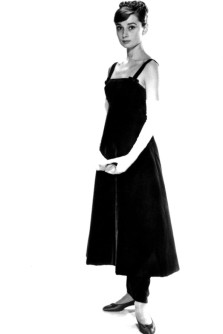 1957 - In a Givenchy black gown and slim trousers