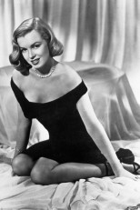 1950 – Wearing an off-the-shoulder dress for an alluring shot taken on the set of film Asphalt Jungle.